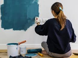 Woman sitting on floor painting walls blue