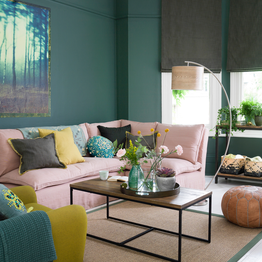 Modern lounge room with pink couch and green wall