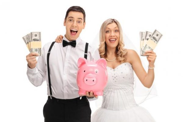 bride and groom holding a piggy bank and cash