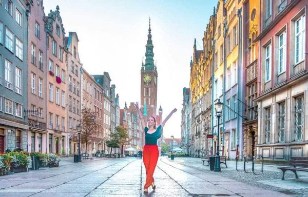 a woman standing in the middle of a city gdansk poland
