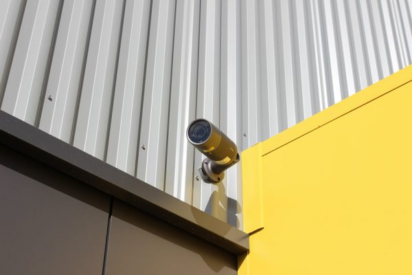 a surveilance camera installed on the wall of a storage facility