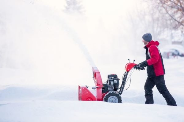 A man operating a snow throwing and removing heavy snow